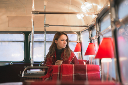 Sweet young girl sits in a cafe bus with a cup of coffee in her hands and looks the window. Woman in a coffee shop with an original retro interior.