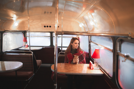 Beautiful woman wrapped in a blanket, sitting in a coffee shop with an original retro interior. Girl is sitting at the cafe bus,holds a cup of coffee his hands and warmes, looking in the window Stockfoto