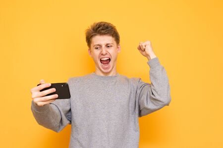 Expressive guy playing games on a smartphone and rejoices in victory on a yellow background. Happy young man holds a smartphone in his hands, looks at the screen and emotionally rejoices. Reklamní fotografie