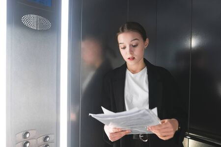 Young concentrated businesswoman in suit thoroughly reading the documents in the elevator. Ambitious office worker is looking at papers and examining thev in the lift. Concentrated woman.