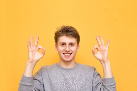 Happy guy on a yellow background smiles at the sign OK. Young man shows what he likes, looks at the camera, isolated on a yellow background. Copyspace