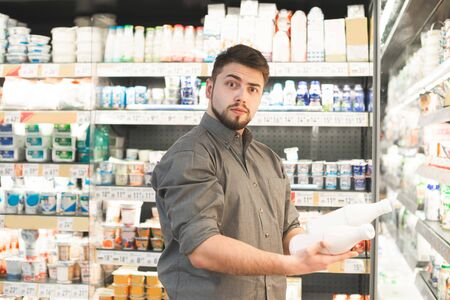 Surprised man with a beard is in the milk department of a supermarket with bubbles of milk in his hands,looking at the camera in amazement.Portrait of an amusing buyer buys products at a grocery store