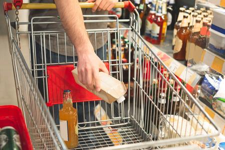 Die Hand des Mannes legt die Produkte in einen leeren Warenkorb. Käufer tätigt Einkäufe in einem Supermarkt. Einkaufen in einem Supermarktkonzept. Kauft Getränke. Hände und Warenkorb Nahaufnahme. Mann kauft Alkohol