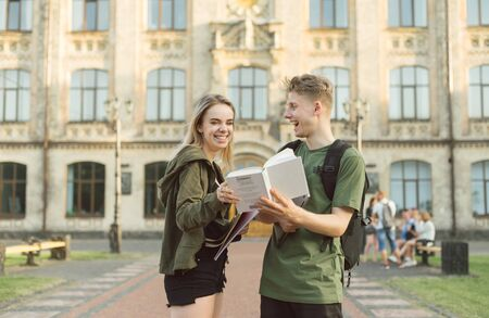 Happy couple standing on background of university building with books and exercise books in hand, guy shows book to girl, she is smiling.Happy couple of students communicating on university background 版權商用圖片