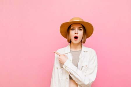 Surprised pretty girl in light summer wears and hat isolated on pink background, looks in camera with emotionless face and points finger aside on empty space. Copy space