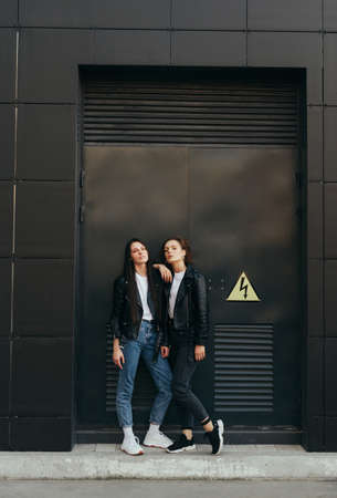 Vertical photo of 2 stylish young girls in leather jackets standing on black background and posing at camera. Street photo of two girlfriends on dark wall background. Copy space