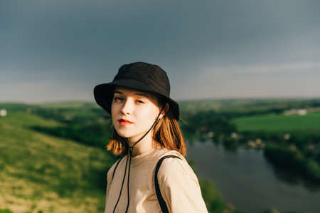 Close portrait of an attractive girl tourist in casual clothes standing on a mountain against the backdrop of a lake at sunset, and looking at the camera with a serious face. Domestic tourism