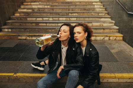 Portrait girls in leather jackets and jeans drinking wine from a bottle on the stairs in the subway and posing at camera, fashionable portrait. Streetwear models drink wine and sit on the stairs