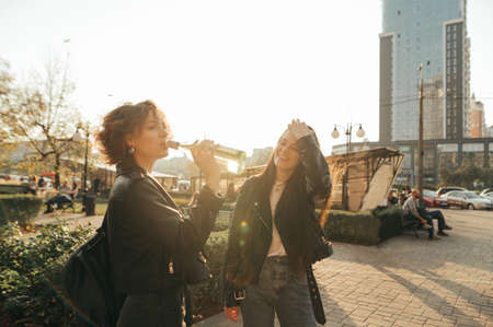 Happy two girls in casual clothes are standing outside at sunrise and drinking wine from bottles, smiling on cityscape background and wearing leather jackets. Freedom girls have fun on a walk.