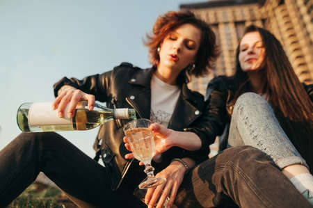 Closeup photo of a girl pours wine from a bottle into a glass on the street. Focus on the girl's hands with a bottle of wine and a glass. Girlfriends drinking wine at sunset. Background Copy space