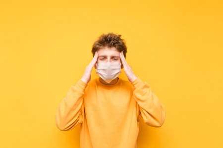 Guy in the medical mask looks at the camera and puts his fingers to his temple from the headache. Young man in a protective mask suffers from a headache. Coronavirus pandemic. Quarantine covid-19. 免版税图像