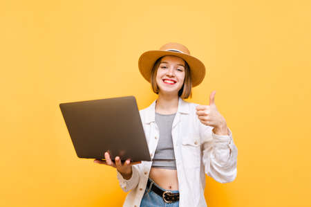 Portrait of happy lady and light summer clothes and hat stands on yellow background with laptop in hands, looks into camera and smiling, shows thumbs up. Copy space. Isolated.