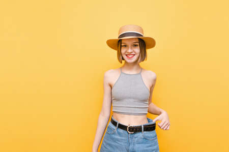 Sporty skinny girl in a hat stands on a yellow background and shows the result of the workout, pulls the large size of pants from the body. Attractive lady shows the result of losing weight on large pants