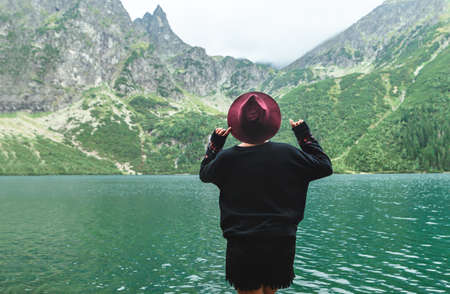 Back of a stylish girl in dark clothing on a background of a mountain lake with blue water and mountains with clouds. Background Hipster tourist woman on the shores of Lake Morskie Oko