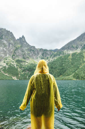 Background Vertical photo. The person in the yellow raincoat stands in against the backdrop of a beautiful landscape with Lake Morskie Oko in the Tatra Mountains, admiring the view. Hiking mountains