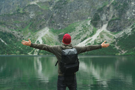 Hiker in casual clothes and with a backpack stands with his hands raised on the background of the lake in mountains and looks at the unreal view. Tourist has reached the place of travel and rejoices