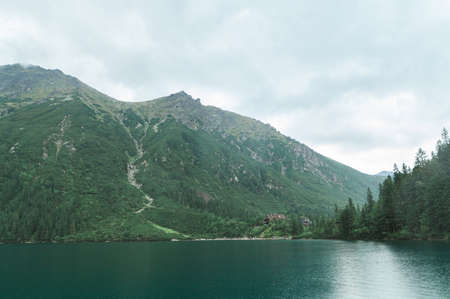 Landscape of a mountain lake with blue water in the rain with a wooden tourist house. Lake Morskie Oko, view of a wooden house. Tatra Mountains. Background