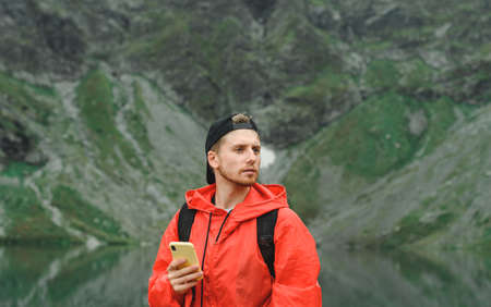 Closeup portrait of a young man in a red raincoat stands with a smartphone in hand on a background of mountains, looking away. Guy tourist in a hat stands in the mountains and uses the Internet.