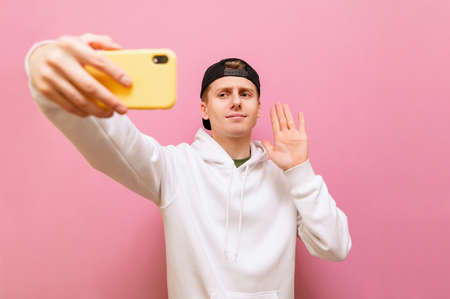 """Young man in casual clothes makes a video call on a smartphone on a pink background, looks in camera of phone and is greeted with a palm raised. Guy makes a phone call and shows """"Hello"""" gesture"""