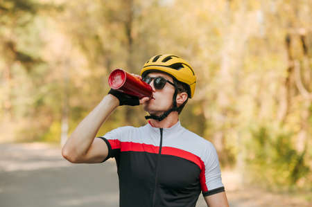 Handsome cyclist man in sunglasses and helmet drinking water from red bottle in autumn park. Thirsty cyclist drinks water after a workout on a bicycle against the backdrop of an autumn landscape. Imagens
