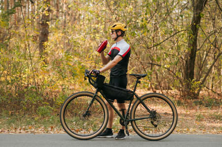 Man in sportswear standing in autumn forest with bicycle and bottle of water in his hands and looking away. Athlete weightlifter is resting in training, drinking water from a bottle. Imagens