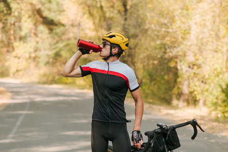Portrait of a thirsty cyclist in a sports outfit standing on the road outside in the fall, drinking water from a red bottle and resting. Tired cyclist is resting, quenching his thirst for water. Imagens