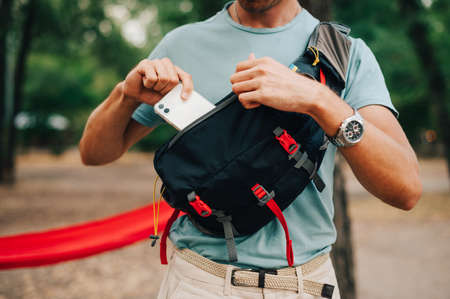 Close photo of a waist bag for advertising. A man in casual clothes puts a white smartphone in the pocket of his waist bag.