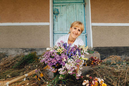 Happy female farmer in the country with a bouquet of dried flowers in her hands posing for the camera with a smile on her face. Smiling florist with dried flowers in hands posing at camera