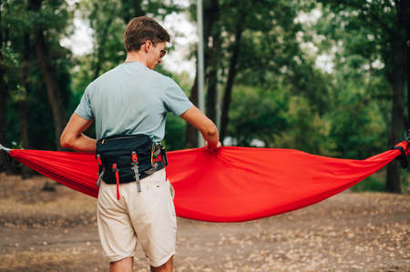 A young man in a waist bag stands in the park and adjusts the hammock with his hands. Male hiker in summer casual clothes straightens a hammock in the woods