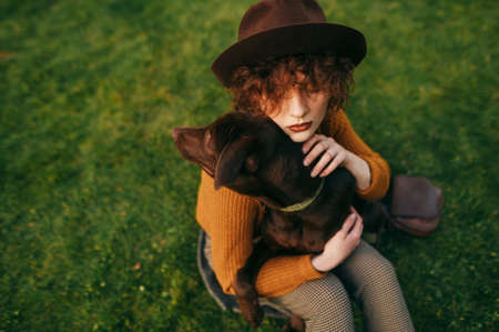 Closeup portrait of stylish lady in hat and with curly hair hugging dog on lawn background, top view. Owner loves her dog, sits on the lawn and hugs the pet. Copy space
