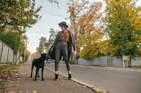 Stylish lady in vintage clothes posing at camera with dog on leash on the background of town street in autumn season. Curly lady in a hat walks a dog on the village street. Stock fotó