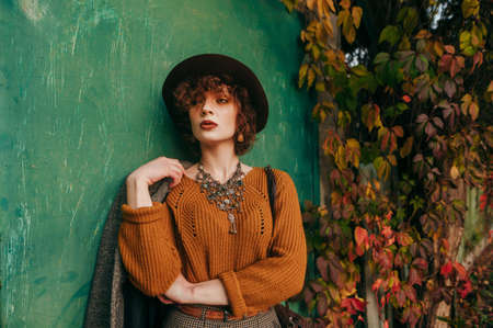 Fashionable lady in vintage clothing stands on background of green grunge wall and yellowed autumn ivy and looks side with a serious face. Model curly girl posing in the city on a rustic background. Archivio Fotografico