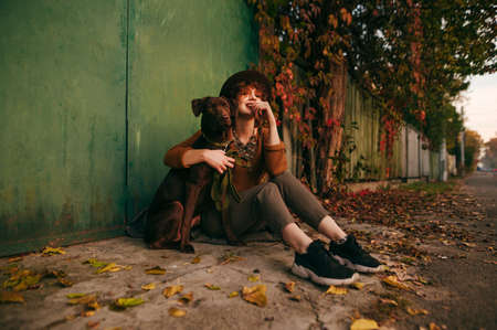 Autumn portrait of a girl in stylish vintage clothes relaxing with a dog outdoors on a background of green wall and and bushes with yellowed leaves. Portrait of a girl with a dog sits on the ground.