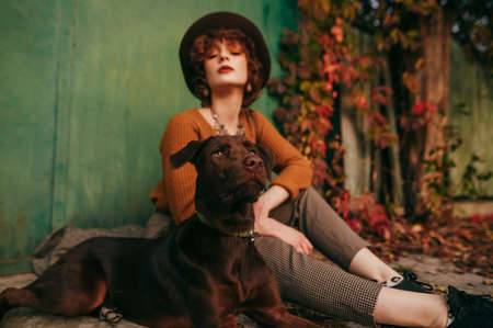 Portrait of a beautiful dog sitting with the owner on the ground in the village on a background of autumn yard, looking away, girl blurred on the background. Pet and fashionable owner autumn photo.