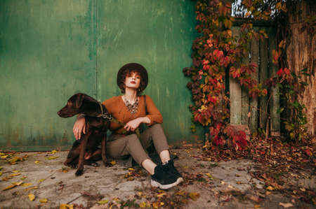 Stylish rural girl sitting on a grunge green wall background with ivy with a dog posing at the camera with a serious face. Fashion photo of lady with dog on country house background in autumn day. Stock fotó