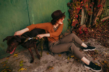 Happy lady in trendy vintage clothes sits on the ground in the yard of a country house and plays with a playful dog in the autumn day. Smiling owner having fun with dog on street near country house.
