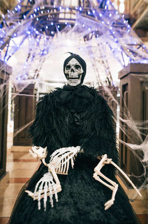 Skeleton of a woman with the bones of an animal in her arms indoors on a background of lights. Halloween decorations. Vertical.