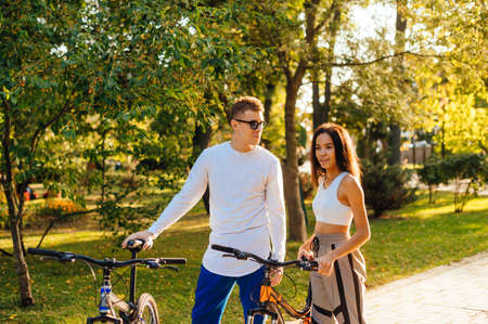 Beautiful woman and man in bright casual clothes walking with bicycles in the autumn park and talking. Young couple playing bicycles in the park.