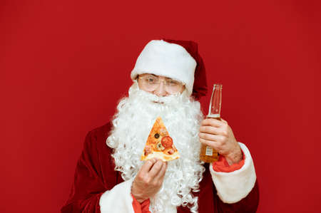 Closeup portrait of positive man in santa claus costume isolated on red background, holding slice pizza and bottle of beer, looking into the camera and smiling. Santa eats fast food and drink alcohol Stock Photo