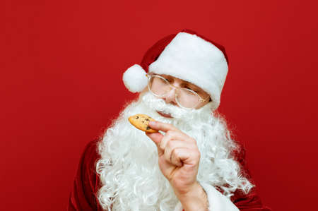 American Santa Claus with chocolate chip cookies in hand isolated on red background, closeup portrait. Beautiful Santa with glasses eating delicious Christmas cookies. New Year and Christmas concept