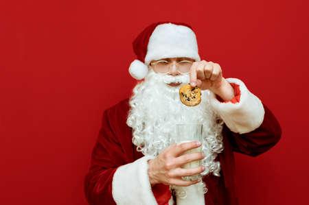 Beautiful Santa eating cookies and milk on a red background, puts cookies in glass. Christmas and New Year concept. Santa Claus and cookies with milk. Isolated. Background Stock Photo