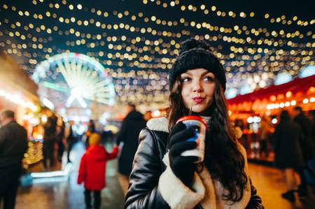 A pretty girl in a hat and winter clothes walks down the Christmas street in the evening and drinks a hot drink from a paper cup. Lady stands at a decorated Christmas market in the evening.