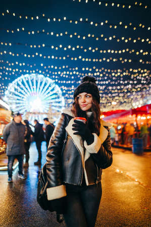Attractive girl in warm clothes stands at the evening fair decorated with lanterns with a cup of hot drink, looks to side on a background of garlands on a Ferris wheel.Lady at the Christmas market
