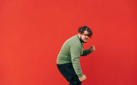 Expressive curly fat man listens to music on headphones and dances on a red background, isolated. 免版税图像