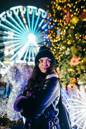 Evening portrait of a cute lady standing on the street against the backdrop of the main Christmas tree and the Ferris wheel, looking away and smiling. Evening walk at Christmas.
