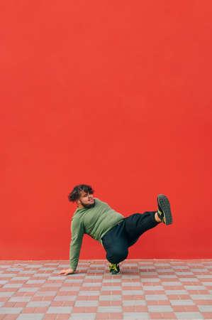 Overweight technical dancer dances break dance on red wall background. Vertical.