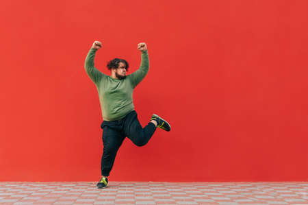 Portrait of funny fat dancer in casual clothes dancing on red wall background and looking aside at empty space, isolated. A man with excess weight dances funny dances.