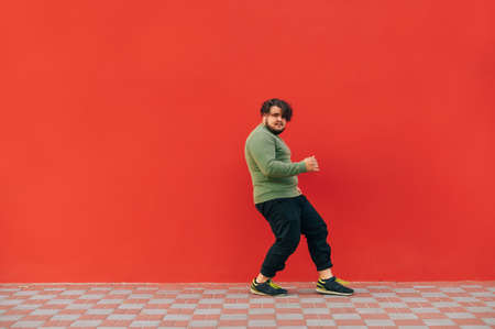 Charismatic overweight young man in green sweatshirt dancing hip hop on red background and listening to music in wireless headphones.
