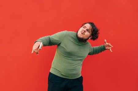 Charismatic fat man with curly hair in casual clothes dancing on a red background and listening to music on headphones. Isolated.