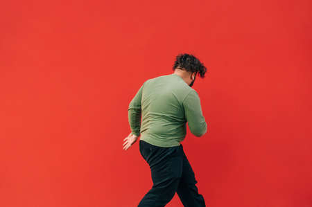 Back of a fat stylish guy dancing hip hop on a red wall background. An overweight man dances hip hop. Isolated.